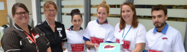 Fundraisers holding a cake at a bake sale