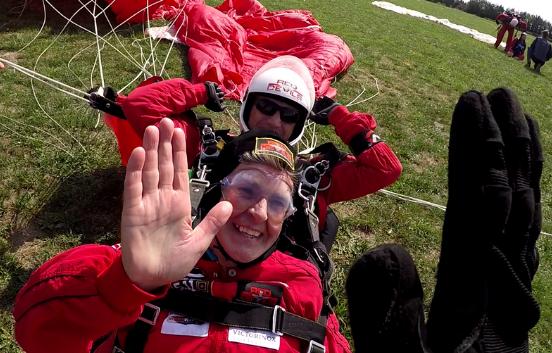 Skydivers high five after landing
