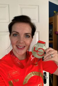 A fundraiser holds up a marathon medal